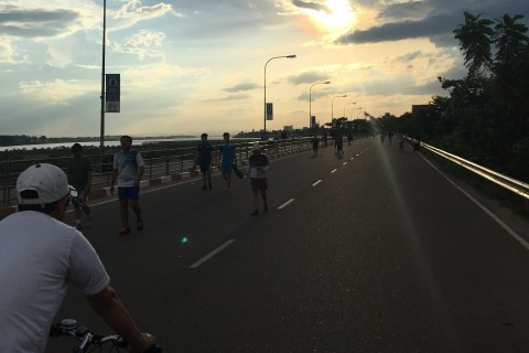 Locals take to the boulevard at the end of the day. Photo taken in or around Mekong riverfront at sunset, Vientiane, Laos by Samantha Brown.